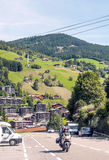 Moto driving in the road. With Albertville in the French Alps in the background. Houses are surrounded by meadows.  It is a vertical picture on a sunny day Royalty Free Stock Images