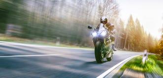 Moto en el montar a caballo del camino divertirse que monta el camino vacío o Fotografía de archivo