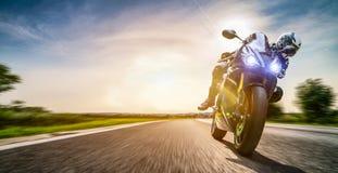 Moto en el montar a caballo del camino divertirse que monta el camino vacío en un viaje/un viaje de la motocicleta imagenes de archivo