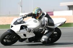 Moto en la pista, inclinándose en curva sostenida imagenes de archivo