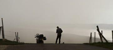 Moto et cavalier debout silhouettés contre une vallée brumeuse images stock