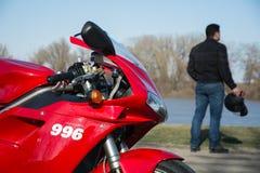 Moto et conducteur de Ducati de sport avec le casque Photographie stock