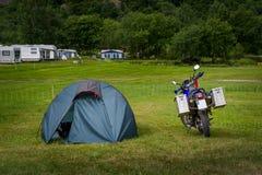 Moto et tente du ` s de cavalier au camping Photographie stock