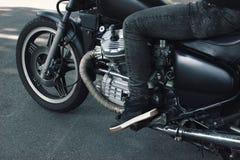 Moto faite sur commande montée des années 1980 noires de vintage sur le trottoir Photo libre de droits