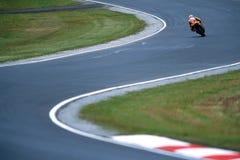 Moto GP. A Moto GP bike cruises down the track shaped as an S curve Stock Photo