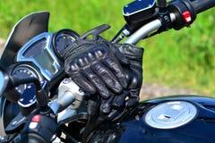 Moto-Handschuhe auf den Lenkstangen des Motorrades lizenzfreies stockbild