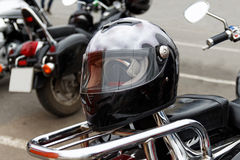 Moto helmet on motorcycle. Black moto helmet motorcycle and motorbikes on blurred background Stock Images