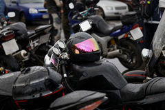 Moto helmet on motorcycle. Moto helmet with drop of water on motorcycle and motorbikes on blurred background. Shallow focus Stock Photography