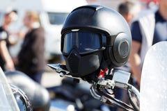 Moto helmet on motorcycle handlebars. Against blurred background Stock Photo