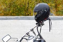 Moto helmet on motorcycle handlebars. Black moto helmet on motorcycle handlebars against blurred background Stock Image