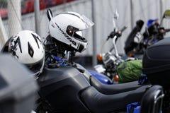 Moto helmets on motorcycle handlebars. White moto helmets on motorcycle handlebars against blurred background Royalty Free Stock Images