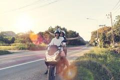 Moto heureuse d'équitation de couples dans le voyage de femme excité par campagne et d'homme sur le voyage par la route de motocy Image stock