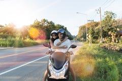 Moto heureuse d'équitation de couples dans le voyage de femme excité par campagne et d'homme sur le voyage par la route de motocy Photo stock