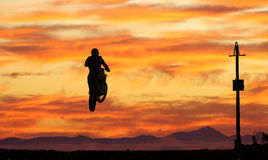 Moto x landscape. Moto cross rider jumping,silhouetted against sunset,open landscape stock photo