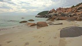 Moto lungo il mucchio delle rocce sulla spiaggia di sabbia al piede della collina stock footage