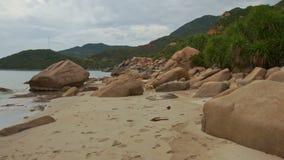 Moto lungo il mucchio delle rocce sulla spiaggia di sabbia al piede della collina video d archivio