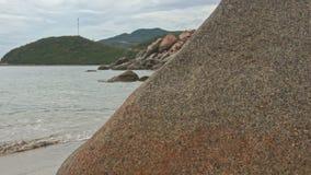 Moto lungo il mucchio delle rocce sulla spiaggia di sabbia al piede della collina archivi video