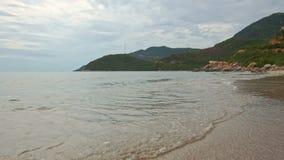 Moto lungo la spuma di Wave sulla spiaggia di sabbia con le piante al piede della collina stock footage