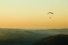 Moto paraglider ovanför landskapet Arkivbild