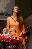 Moto Park 2015 Beautiful brunette model in an orange suit riding a motorcycle. Moto show Royalty Free Stock Photo