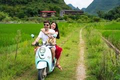 Moto que monta de los pares alrededor de campos del arroz de Yangshuo, China imagenes de archivo