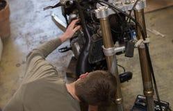 Moto que repara por el hombre joven hermoso en su anillo del garaje Foto de archivo