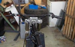 Moto que repara por el hombre joven hermoso en su anillo del garaje Imagenes de archivo