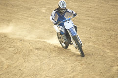 Moto racer. A cross-country motorcycle race over a closed course of rough terrain with steep hills and sharp curves Royalty Free Stock Photos
