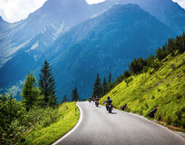 Moto racers on mountainous road. Moto racers riding on mountainous road, drive a motorcycle, summer adventure, extreme sport, travel to Europe, active lifestyle Royalty Free Stock Image
