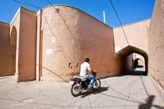 Moto-Radfahrer-Antriebsabflussrinne die schmale Straße Lizenzfreie Stockbilder
