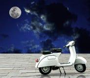 Moto retra blanca con la Luna Llena en cielo nocturno. Imagen de archivo