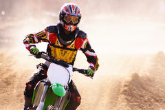 Moto x rider cu. Close up of moto cross rider,backlit,dust softens background royalty free stock image
