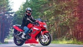 Moto roja con el jinete que se sienta en ella almacen de video