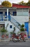 Moto roja delante de la casa griega típica Foto de archivo libre de regalías