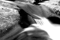 Moto vago e fotografia lenta di Waterscape dell'otturatore di un fiume che precipita sopra una pietra Immagine Stock