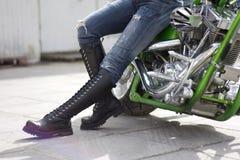 Moto verte et une femme dans les gaines lourdes Images stock