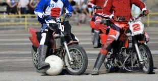 Motoball, spelers speelt motoball op motorfietsen met een bal, twee spelers stock afbeeldingen
