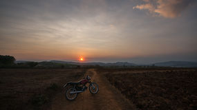 The motobike on the field, sunset in country and beatyful cloud on sky Dalat city - in LamDong- VietNam. The motobike on the field, sunset in country and Royalty Free Stock Image