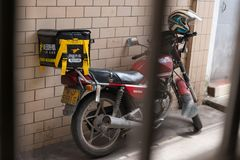Motobike with Meituan food delivery case parking on the street. Zhongshan,China-May 12,2018:motobike with Meituan food delivery case parking on the street.Food stock image