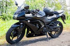 Motobike nero parcheggiato sul bordo della strada Fotografia Stock