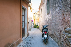 Motobike scooter parked in a typical narrow old street in Sicile Stock Photos