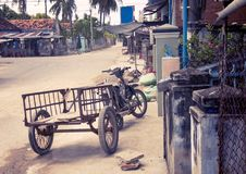 Motobike in the Vietnamese village, adapted for cargo transportation. A picturesque village street. With toning. Stock Photo