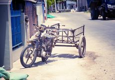 Motobike in the Vietnamese village, adapted for cargo transportation. A picturesque village street. With toning. Royalty Free Stock Images