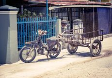 Motobike in the Vietnamese village, adapted for cargo transportation. A picturesque village street. With toning. Stock Photography