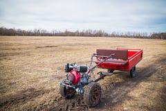Motoblock avec une remorque allant sur une route de champ au printemps en mars, la nouvelle saison des travaux sur le terrain images libres de droits