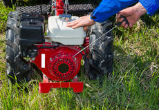 Motoblock include. Close-up, the farmer includes tillers, inspection, repair Stock Photo