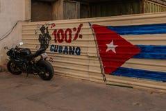 A motocicleta é estacionada perto da cerca, onde os desenhos são feitos: a bandeira de Cuba, grafitti na cerca com a inscrição Imagens de Stock