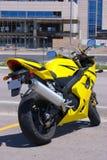 Motocicleta amarela estacionada pela construção Foto de Stock Royalty Free