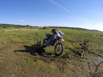 Motocicleta con el jinete que se coloca en campo Fotografía de archivo