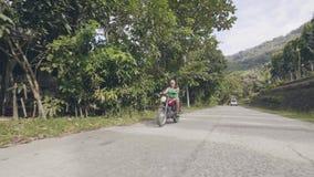 Motocicleta da equitação do homem superior na estrada na paisagem tropical da vila Homem maduro que conduz o velomotor quando via filme